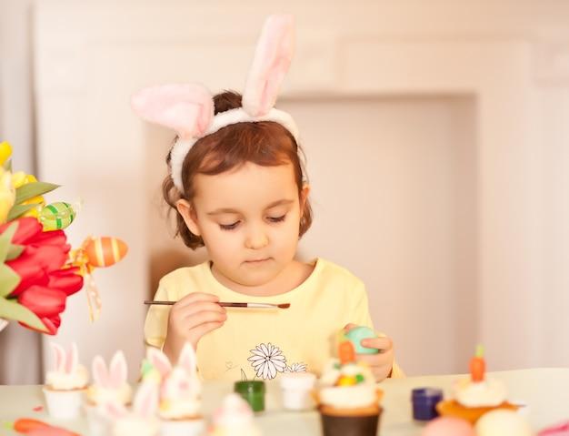 Garota engraçada usando orelhas de coelho e pintando um ovo de páscoa na primavera em casa.