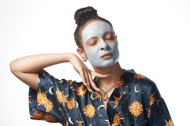 Garota engraçada yong com máscara de beleza de argila no modelo de pele isolado