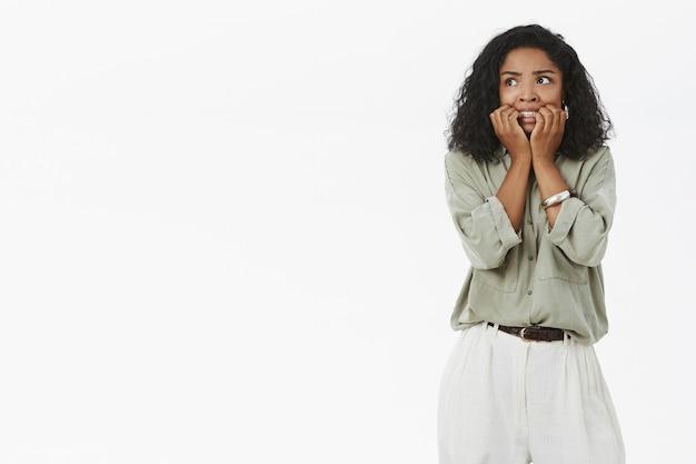 Garota enlouquecendo sentindo medo e tremendo de medo roendo as unhas de ansiedade olhando para a esquerda intensa