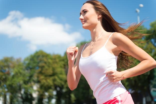 Garota ensolarada ao ar livre no céu azul. treinador ou treinador em treino. esporte e boa forma saudável. corredor em competição e sucesso futuro. mulher correndo na pista da arena.