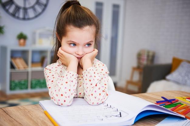 Garota entediada e triste fazendo lição de casa em casa