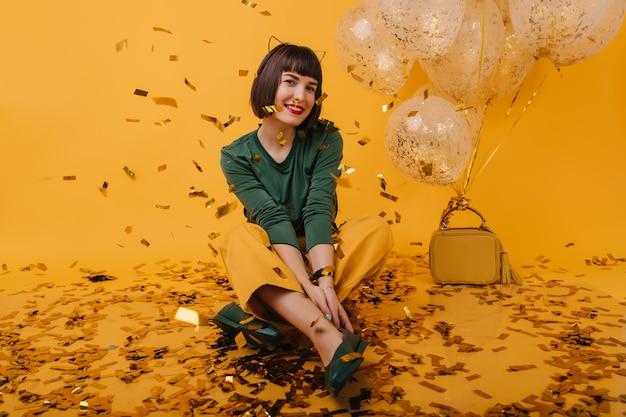 Garota entusiasmada com corte de cabelo curto, posando após a festa de aniversário. modelo feminino branco sentado ao lado de balões.
