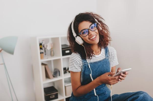 Garota entusiasmada com uma camisa listrada ouvindo música em frente à parede com prateleiras atrás