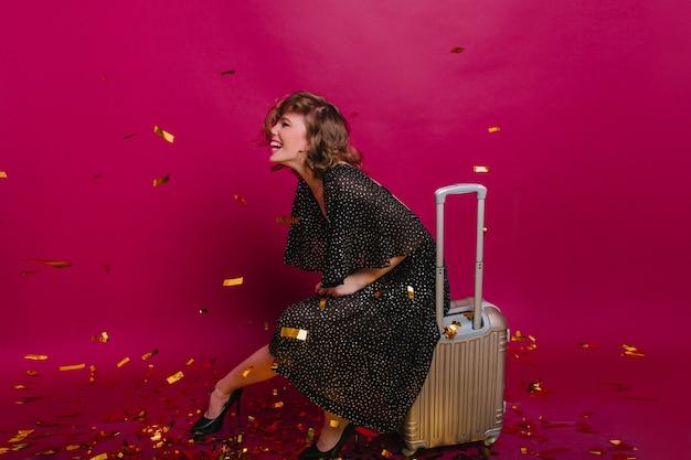 Garota entusiasmada de cabelos curtos em um vestido da moda se divertindo na festa antes da viagem