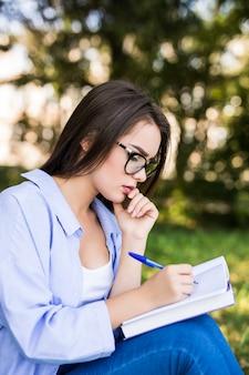 Garota entusiasmada de jaqueta jeans e óculos lê um livro contra o parque verde de verão.