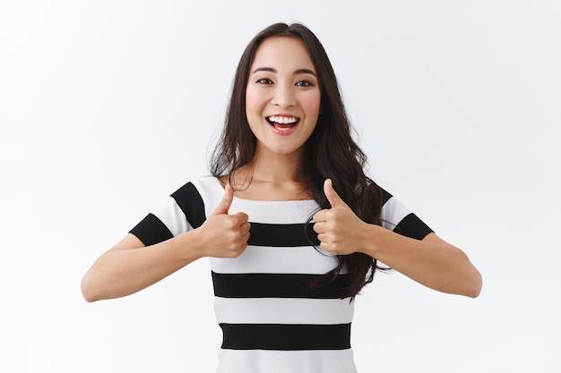 Garota entusiasmada incentive o amigo a acompanhar. garota oriental atraente com camiseta listrada mostrando polegar para cima e sorrindo animada, tipo plano incrível, aprovar a ótima ideia, apoiar fundo branco