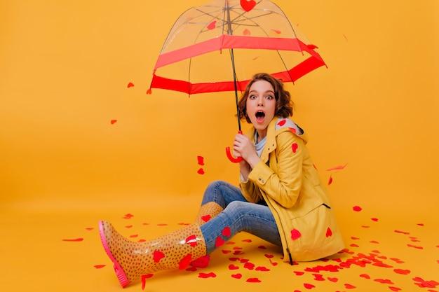 Garota entusiasmada surpresa com sapatos de outono de borracha, sentada no chão. retrato de estúdio de feliz modelo feminino posando, rodeado por corações de papel.