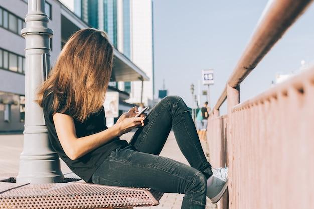 Garota esbelta com cabelo castanho usa um telefone celular