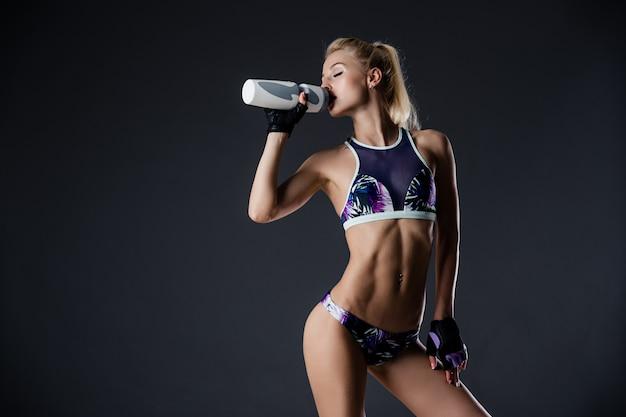 Garota esbelta desportivo água potável, descansando após exercícios de fitness, cansado, copie o espaço