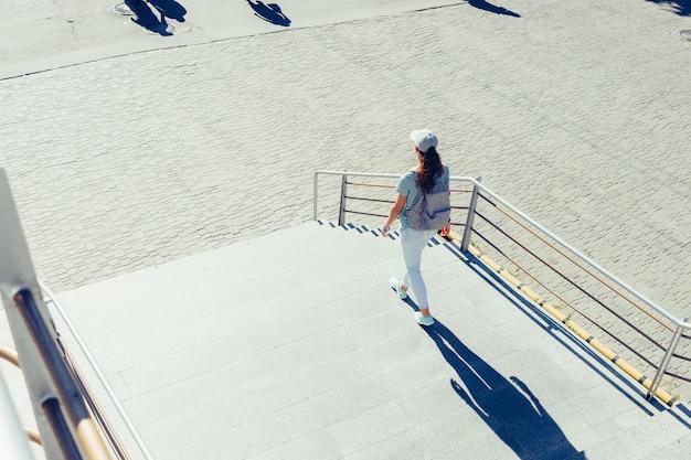 Garota esbelta em um boné e jeans andando nas escadas da cidade no verão