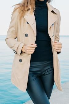 Garota esbelta em um casaco bege e calça preta na praia