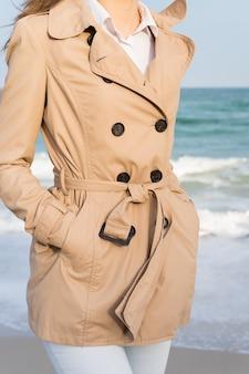 Garota esbelta em um casaco bege e jeans caminhando ao longo da praia no sol de noite