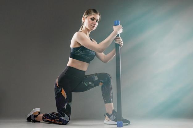 Garota esbelta em um uniforme de esportes investe nas nádegas