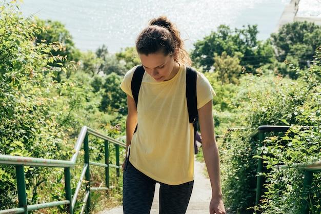 Garota esbelta em uma camisa amarela e com mochila no fundo do mar e árvores