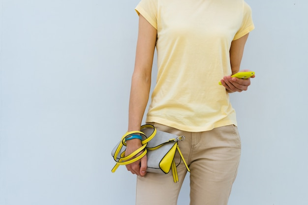 Garota esbelta em uma t-shirt amarela segurando a bolsa da senhora amarela e telefone móvel