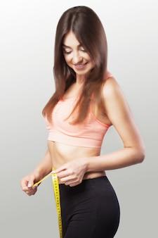 Garota esbelta. mãos para medir a fita da cintura. mulher apta e saudável sobre um fundo cinza.