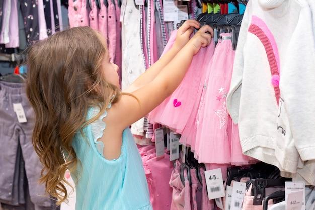 Garota escolhe roupas em uma loja de roupas