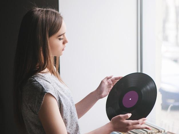 Garota escolhendo discos de vinil retrô na loja de música. estilo hipster moderno, jovem melomaníaca