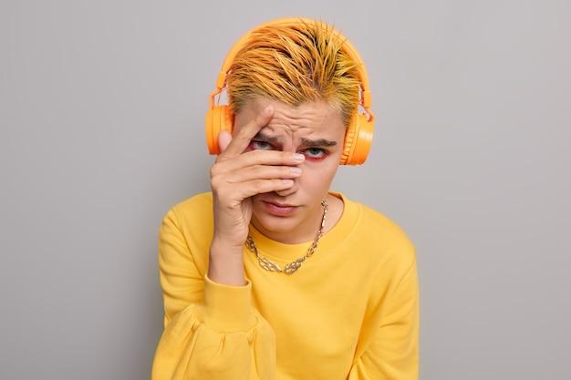 Garota esconde rosto por entre os dedos com expressão decepcionada tem cabelo curto tingido de amarelo vestido com um macacão casual cinza