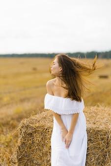 Garota eslava com longos cabelos loiros em um vestido branco de pé em um campo com fardos de palha, o cabelo dela soprando no vento