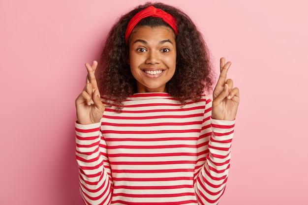 Garota esperançosa com cabelo encaracolado posando com um suéter vermelho listrado