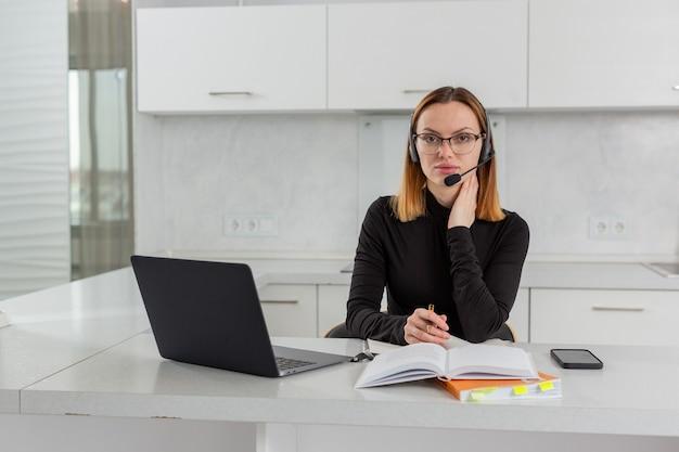 Garota esperta de óculos e fone de ouvido sentada em um laptop no escritório em casa realiza treinamento on-line com foto de alta qualidade