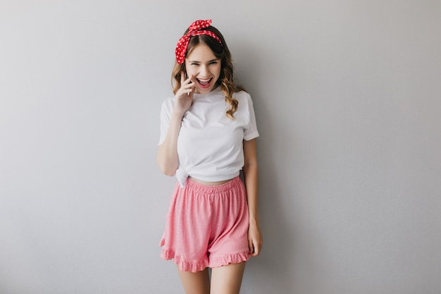 Garota espetacular em shorts rosa rindo. retrato de senhora alegre com cabelo encaracolado isolado.