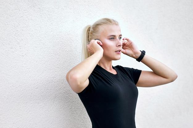 Garota esportiva atraente vestindo sportswear preto, ouvindo o misic. tiro ao ar livre em fundo de parede branca.