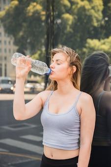 Garota esportiva bebendo água