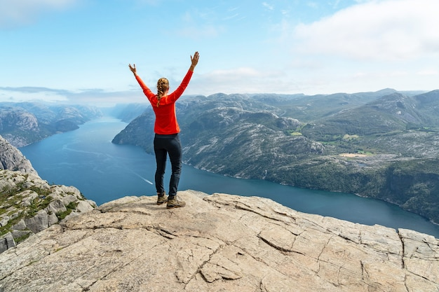 Garota esportiva com as mãos levantadas, de pé na rocha perto de preikestolen, noruega, vista para o mar de lusefjord.