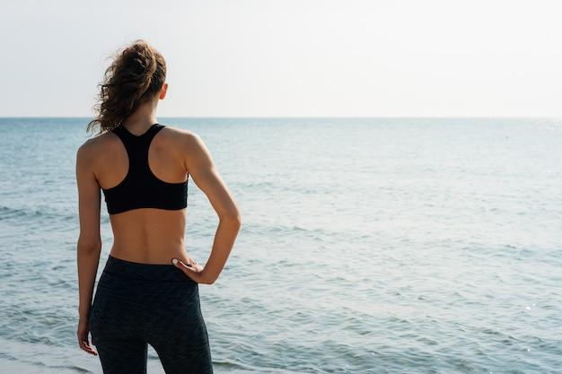 Garota esportiva com cabelo encaracolado em um sutiã esportivo em pé na praia e olhando para o mar pela manhã