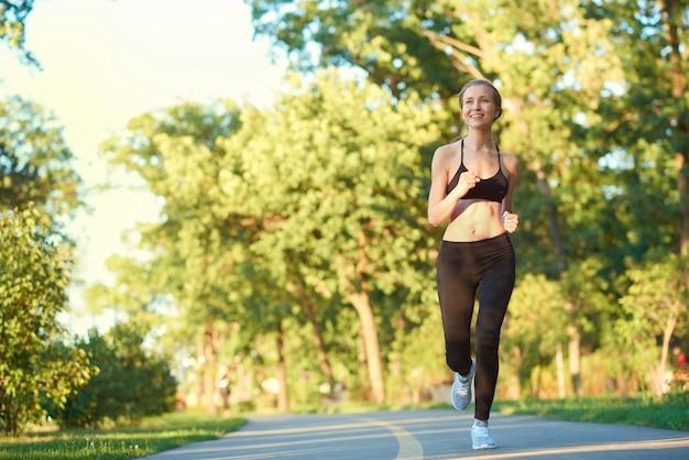 Garota esportiva correndo ao longo da pista no parque da cidade.