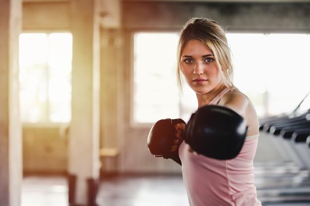 Garota esportiva de retrato mulher bonita com as luvas de boxe de volta treinando na academia