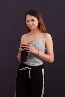 Garota esportiva depois de jogar bebidas esportivas em uma coqueteleira com uma camisa molhada de suor em um fundo escuro