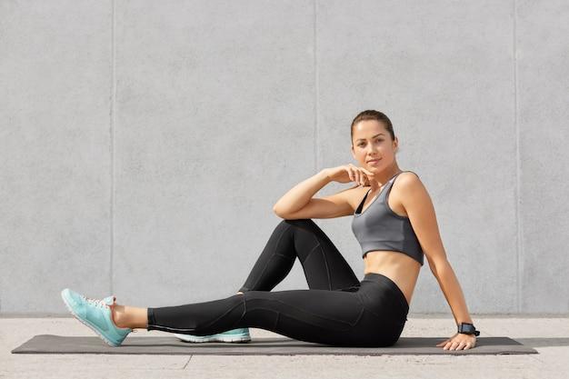 Garota esportiva descansa após exercícios acrobáticos, senta-se no colchonete, usa regata, perneiras pretas e tênis