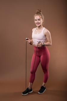 Garota esportiva e apta com cabelo loiro segurando a corda de pular e mantendo uma perna nela enquanto faz exercícios na academia ou centro esportivo