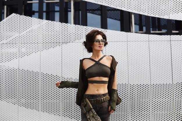 Garota esportiva e sexy morena fitness modelo com corpo perfeito em elegantes óculos escuros e roupa militar, em calças camufladas e em top com ombros nus posando ao ar livre em uma cidade.