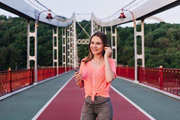 Garota esportiva em fones de ouvido posando no estádio e rindo. mulher bonita ativa se divertindo durante o treinamento ao ar livre no verão.