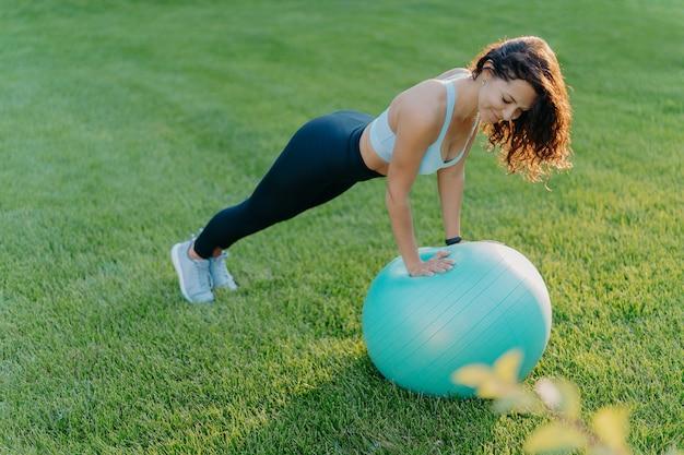 Garota esportiva em pose de prancha na bola de ginástica
