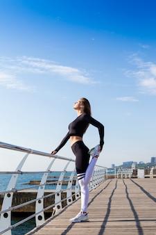 Garota esportiva, estendendo-se perto do mar