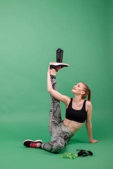Garota esportiva estica e segura uma garrafa de água de uma maneira incomum