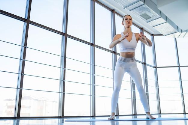 Garota esportiva fazendo exercícios de agachamento
