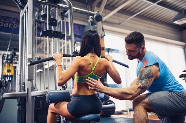 Garota esportiva fazendo exercícios de peso com a ajuda de seu personal trainer na academia.