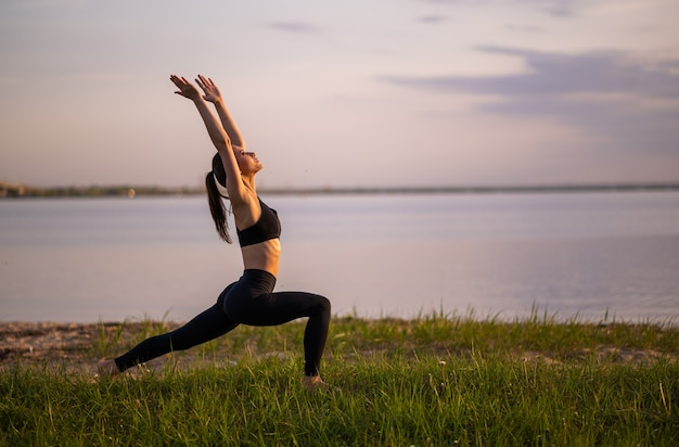 Garota esportiva fazendo ioga na praia