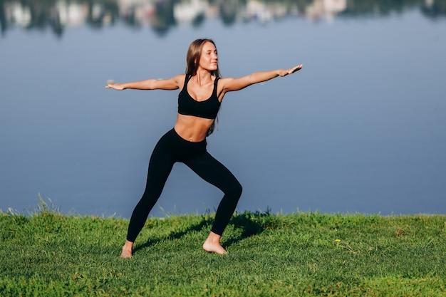 Garota esportiva fazendo yoga asana em pé com as mãos separadas.