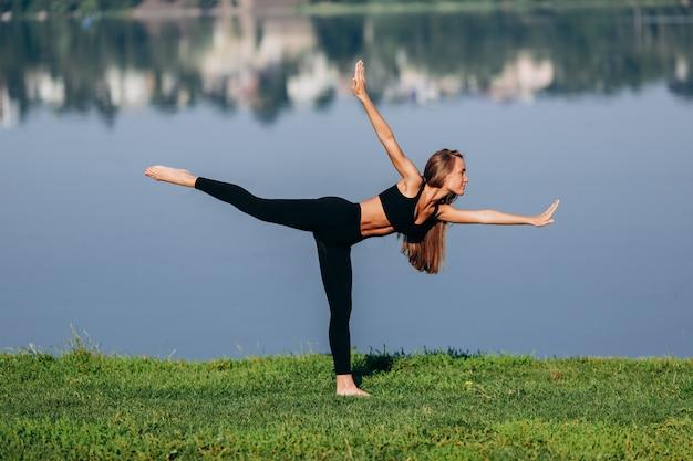 Garota esportiva fazendo yoga asana em pé em uma perna além de suas mãos.