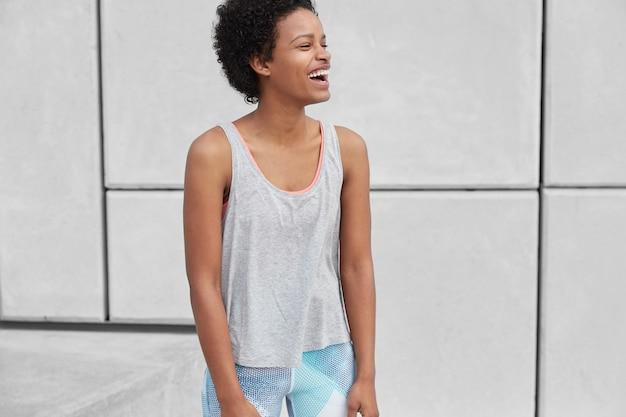 Garota esportiva fitness com pele negra, penteado afro, tem corrida ao ar livre, usa roupas esportivas, sorri e desvia o olhar, posa sobre uma parede branca com espaço de cópia para sua publicidade esportiva. pessoas e corrida