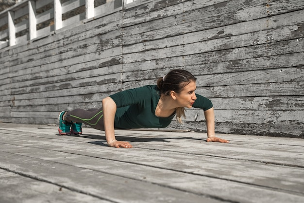 Garota esportiva fitness com roupas esportivas está fazendo exercícios em um fundo de madeira, fundo claro, o conceito de esportes