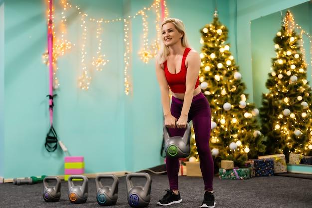 Garota esportiva levanta pesos no ginásio perto de uma árvore de natal decorada, esportes e férias.