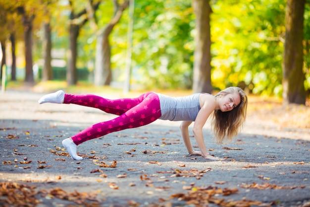 Garota esportiva malhando fazendo flexões pressione o exercício no parque de verão